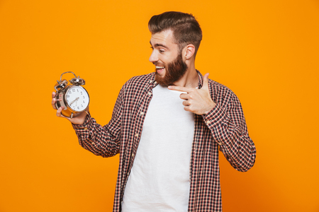 Portrait of a cheerful young man wearing casual clothes standing   holding alarm clock, showing thumbs up