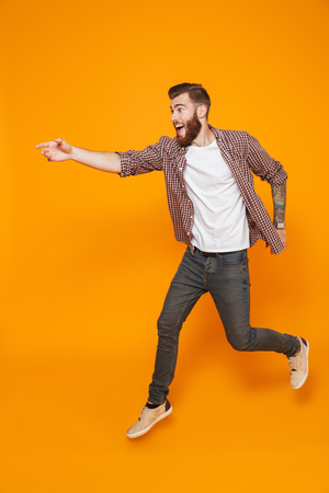 Full length portrait of a cheerful young man wearing casual clothes running away