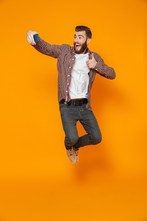 Full length portrait of a cheerful young man wearing casual clothes  jumping, taking a selfie