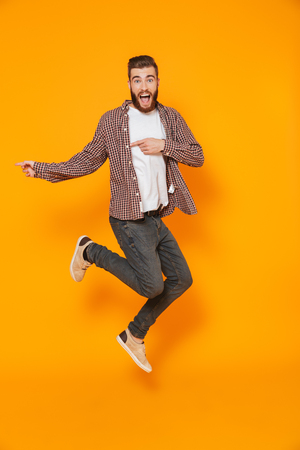 Full length portrait of a cheerful young man wearing casual clothes isolated pointing away at copy space, jumping