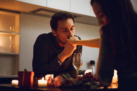 Beautiful passionate couple having a romantic candlelight dinner at home, man kissing hand Фото со стока