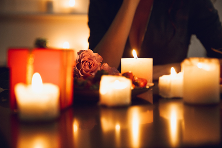 Close up of a woman sitting at the candlelight table