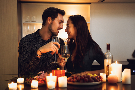 Beautiful passionate couple having a romantic candlelight dinner at home, drinking wine, toasting Imagens