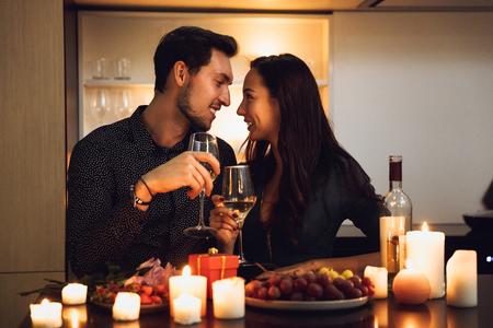 Hermosa pareja apasionada con una cena romántica a la luz de las velas en casa, bebiendo vino, brindando Foto de archivo