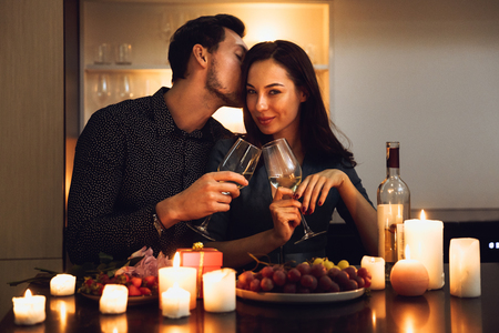 Beautiful passionate couple having a romantic candlelight dinner at home, drinking wine, toasting Standard-Bild