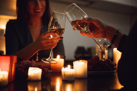 Beautiful passionate couple having a romantic candlelight dinner at home, drinking wine, toasting Archivio Fotografico