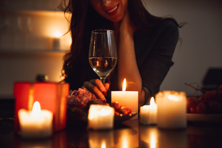 Close up of a woman sitting with glass of wine at the candlelight table