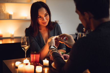 Beautiful passionate couple having a romantic candlelight dinner at home, man making a proposal Stock Photo