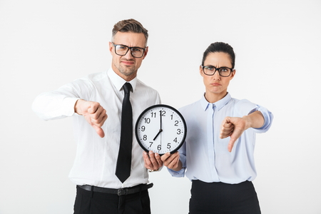 Couple of disappointed colleagues wearing formal clothing standing isolated over white background, showing wall clock, thumbs down Banque d'images - 117548317