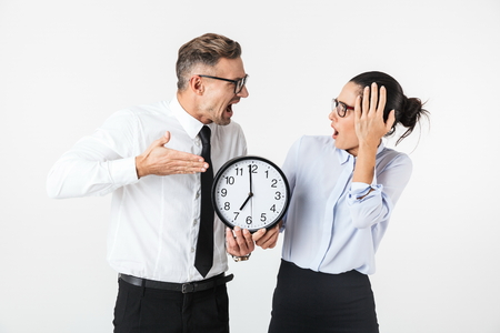 Couple of shocked colleagues wearing formal clothing standing isolated over white background, showing wall clock Banque d'images - 117548322