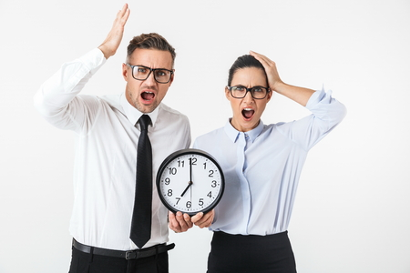 Couple of shocked colleagues wearing formal clothing standing isolated over white background, showing wall clock