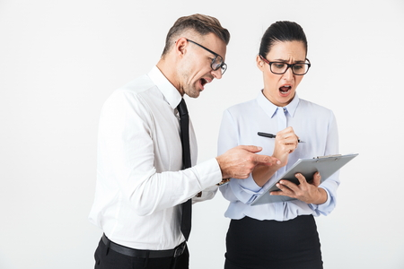 Couple of mad colleagues wearing formal clothing standing isolated over white background, arguing, holding binder Zdjęcie Seryjne