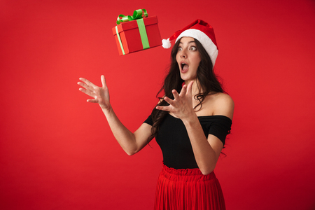 Excited young woman wearing Christmas hat standing isolated over red background, catching flying present box Stock Photo