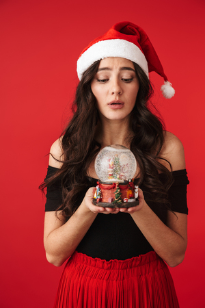 Cheerful young woman wearing Christmas hat standing isolated over red background, holding snowglobe Stock Photo