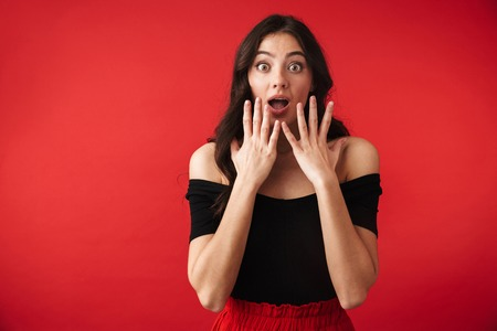Shocked young woman wearing a dress standing isolated over red background, open mouth Stockfoto