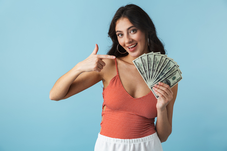 Lovely cheerful girl wearing summer clothes standing isolated over blue background, showing money banknotes
