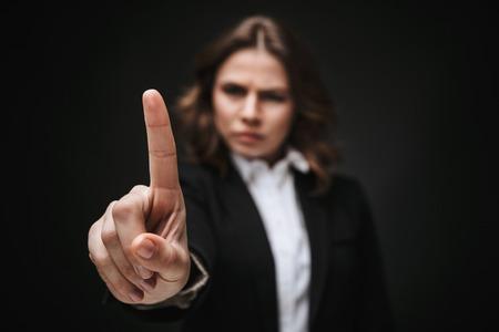 Porträt einer selbstbewussten jungen Geschäftsfrau, die einen formellen Anzug trägt, der isoliert auf schwarzem Hintergrund steht und Zeigefinger zeigt