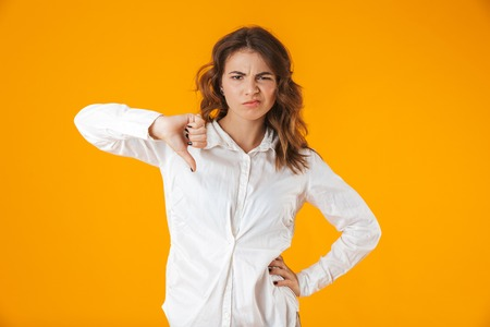 Upset young woman casualy dressed standing isolated over yellow background, thumbs down