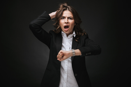 Shocked young businesswoman wearing a suit standing isolated over black background, checking time