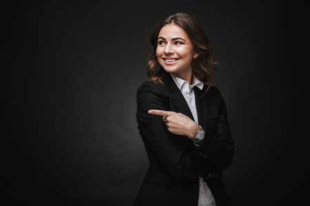 Confident young businesswoman wearing a suit standing isolated over black background, pointing away 版權商用圖片