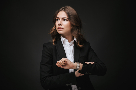 Confident young businesswoman wearing a suit standing isolated over black background, checking time