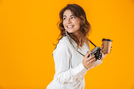 Cheerful young woman casualy dressed standing isolated over yellow background, taking photo with camera, holding takeaway coffee cup Stockfoto