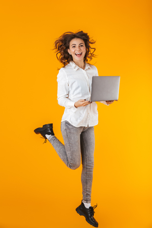 Full length portrait of a cheerful young woman wearing white shirt jumping isolated over yellow background, holding laptop Фото со стока