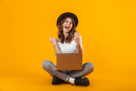 Portrait of a cheerful young woman wearing white shirt and hat sitting isolated over yellow background, using laptop computer Stock Photo