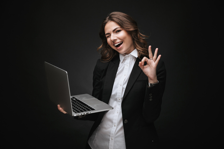 Portrait of a confident young businesswoman wearing formal suit standing isolated over black background, working on laptop