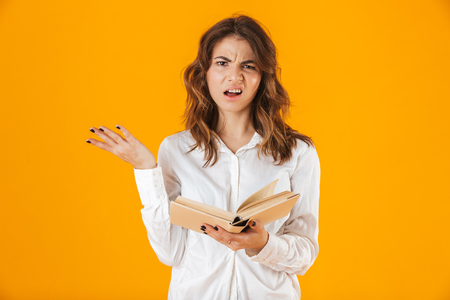 Portrait of a confused young woman wearing white shirt standing isolated over yellow background, holding a book