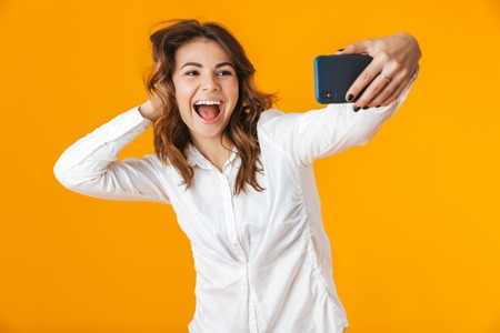 Portrait of a cheerful young woman wearing white shirt standing isolated over yellow background, taking a selfie