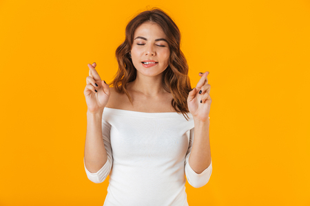 Portrait of a cheerful young woman wearing white shirt standing isolated over yellow background, holding fingers crossed for good luck