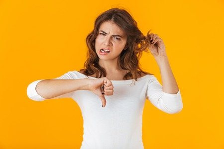 Portrait of an upset young woman wearing white shirt standing isolated over yellow background, holding her hair Zdjęcie Seryjne