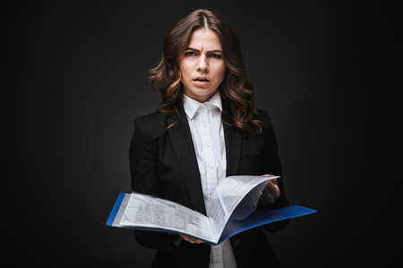 Portrait of a tired busy young businesswoman wearing formal suit standing isolated over black background, holding folder with documents