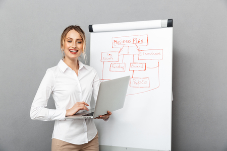 Image of businesslike woman in formal wear using flipchart and laptop while making presentation in the office isolated over gray background Foto de archivo