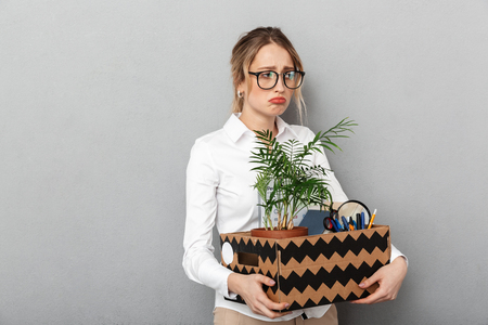 Portrait of sad woman wearing glasses holding box with office stuff isolated over gray background