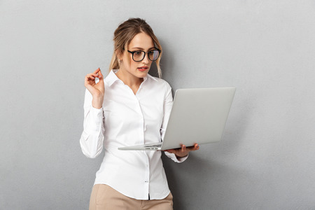 Photo of happy woman wearing glasses standing and holding laptop in the office isolated over gray background