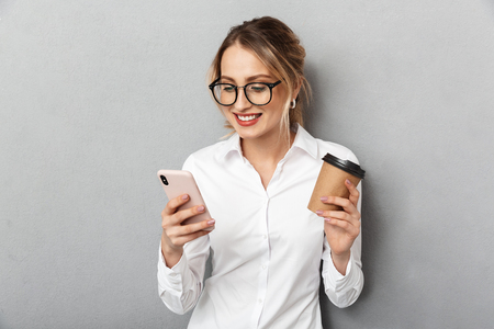 Portrait of happy businesswoman wearing glasses holding smartphone and drinking coffee in the office isolated over gray background