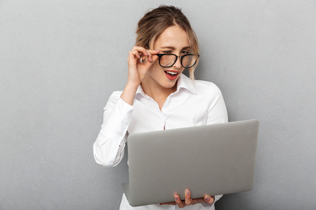 Photo of attractive businesswoman wearing glasses standing and holding laptop in the office isolated over gray background