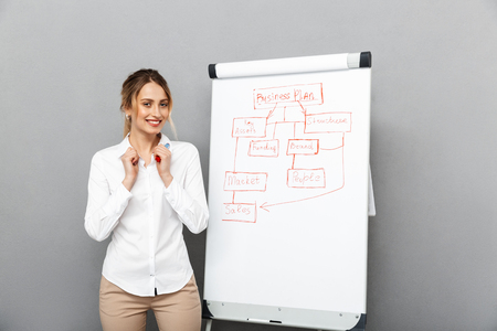 Image of happy businesswoman in formal wear standing and making presentation using flipchart in the office isolated over gray background Stock fotó
