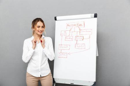 Imagen de feliz empresaria en ropa formal de pie y haciendo una presentación con rotafolio en la oficina aislada sobre fondo gris Foto de archivo