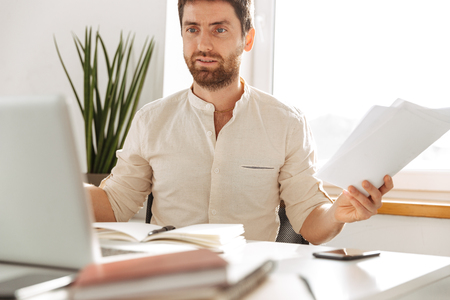 Image of caucasian office worker 30s wearing white shirt using laptop and paper documents in modern workplace Stock Photo
