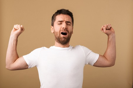 Portrait of a tired young man standing isolated over beige background, yawning