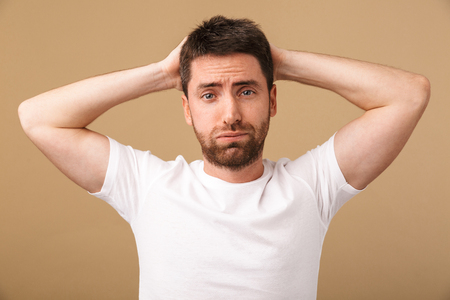 Portrait of a confused young man holding arms on his head isolated over beige background