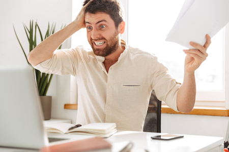Image of stressful office worker 30s wearing white shirt using laptop and paper documents in modern workplace