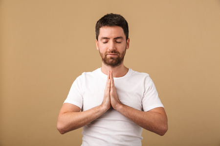 Portrait of a smiling young man standing isolated over beige background, praying Stock Photo