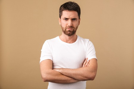 Portrait of an upset young man standing isolated over beige background, arms folded