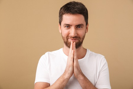 Portrait of a smiling young man standing isolated over beige background, praying Archivio Fotografico