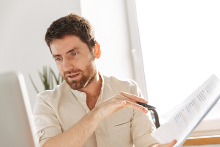 Image of european office worker 30s wearing white shirt using laptop and paper documents in modern workplace