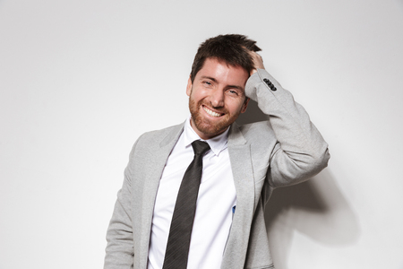 Image of a laughing young businessman in formal clothes isolated over white wall background.